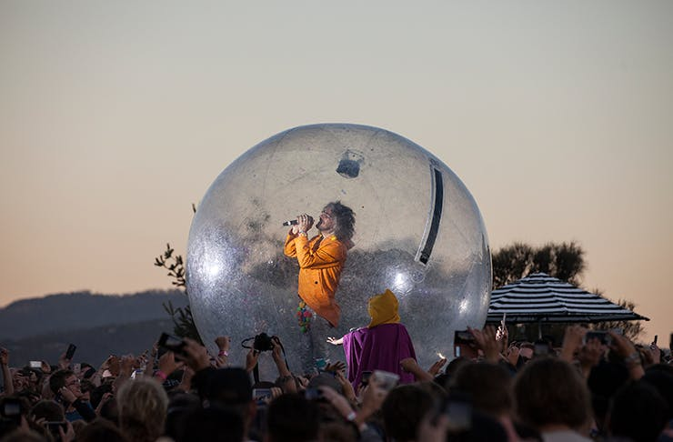 A man singing in a bubble, floating above the crowd.