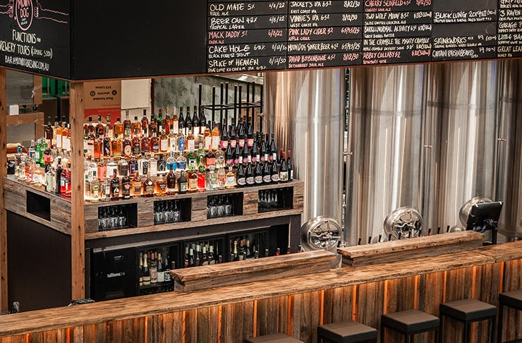 A wooden bar at Moon Dog Brewing stacked with alcohol.
