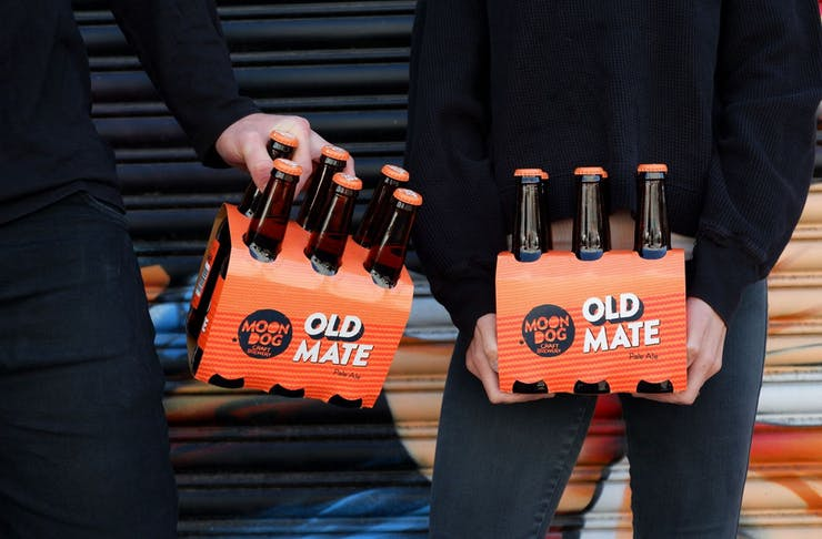 Two people holding six-packs of Moon Dog's Old Mate pale ale.