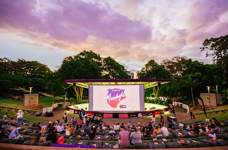 an outdoor ampitheatre facing a large screen