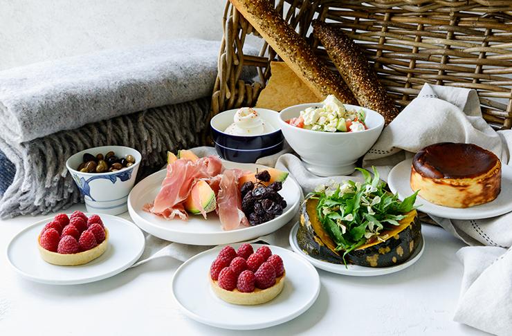 A picnic hamper including a raspberry dessert, prosciutto and cheese.