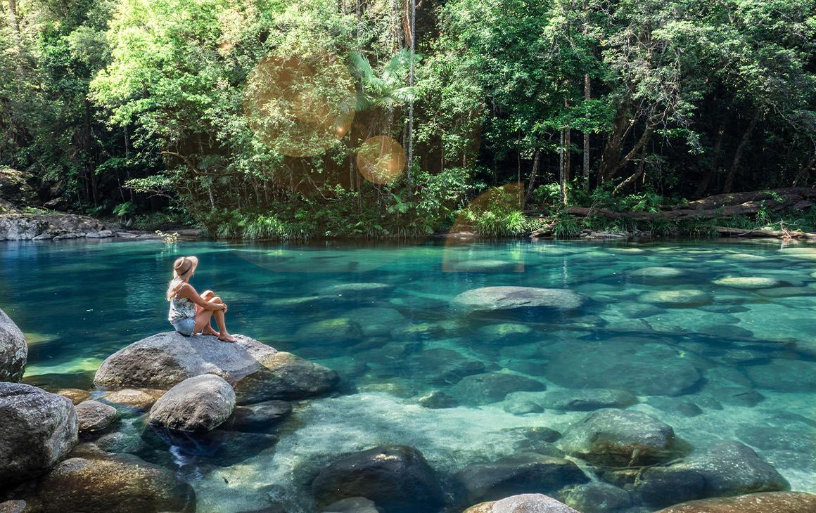 woman sitting by a creek