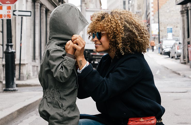 A well-dressed mother embracing her child in the street.