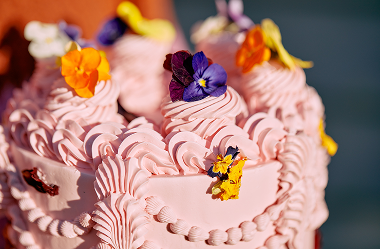 A close up of a cake and bright pink piping.