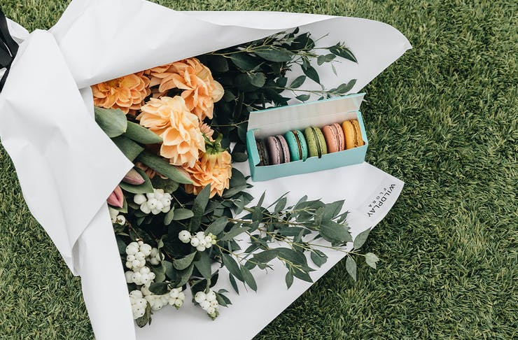 A bouquet of flowers wrapped in white paper sitting on green grass with a box of colourful macarons