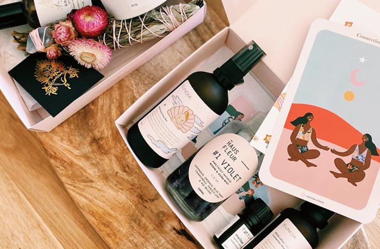 A wellness gift pack in a box, including dried flowers, bottle of calming mist and affirmation cards.