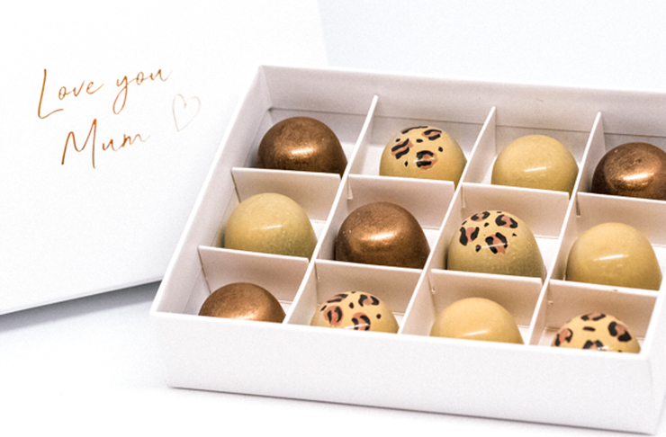 A white gift box filled with rose gold and leopard printed artisan praline chocolates.
