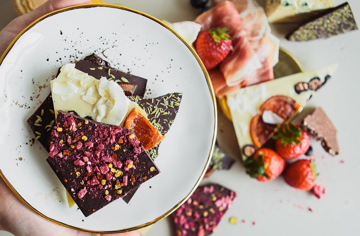 A close up shot of Kokopod's colourful grazing chocolate, broken into pieces on a white plate. Behind, is a blurred cheese and meat platter.