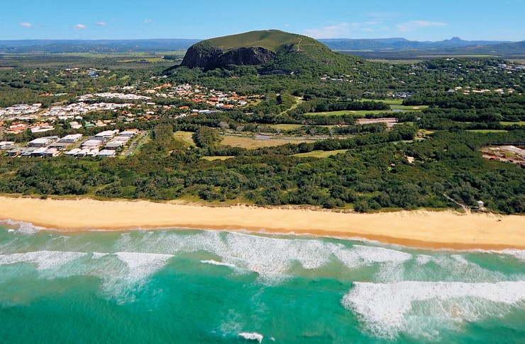 Mount Coolum juts out of the Sunshine Coast landscape, with the ocean in the foreground.