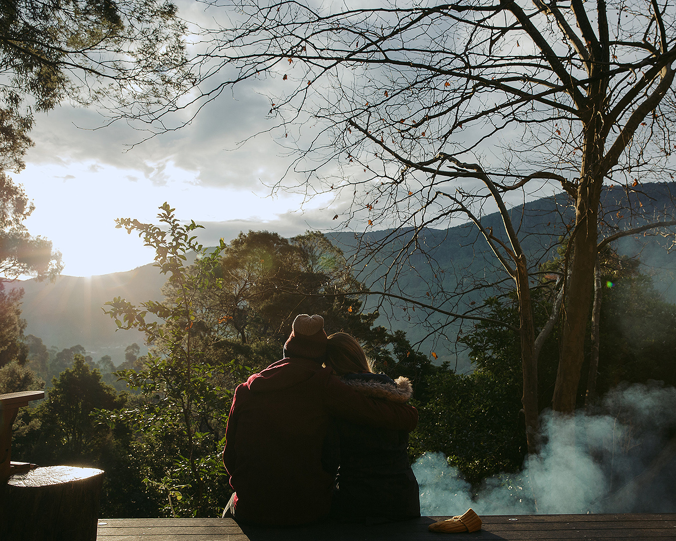 A couple have a cuddle while looking out at the view.