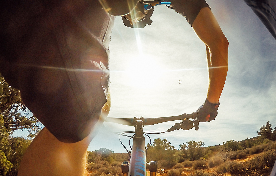 A man rides a mountain bike over rough terrain, we only see the sun and the cross bar.