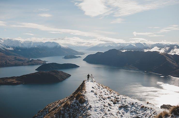 A couple stands atop Coromandel Peak by Mountain weddings