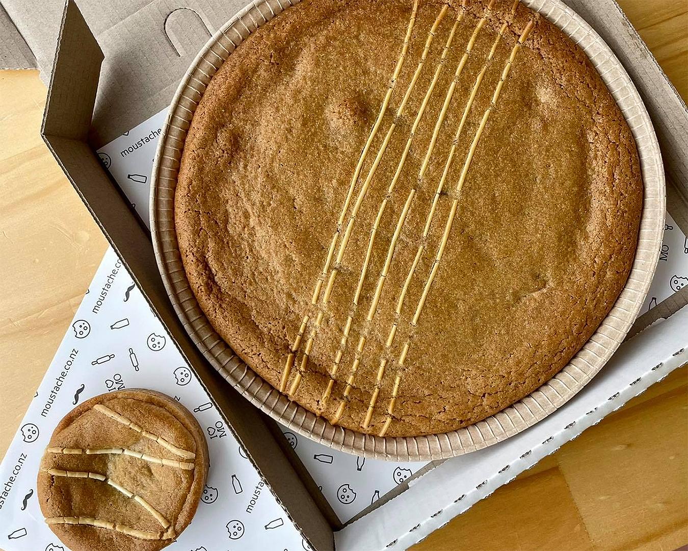 The massive Caramilk cookie pie cake alongside its regular cookie pie sized sibling.