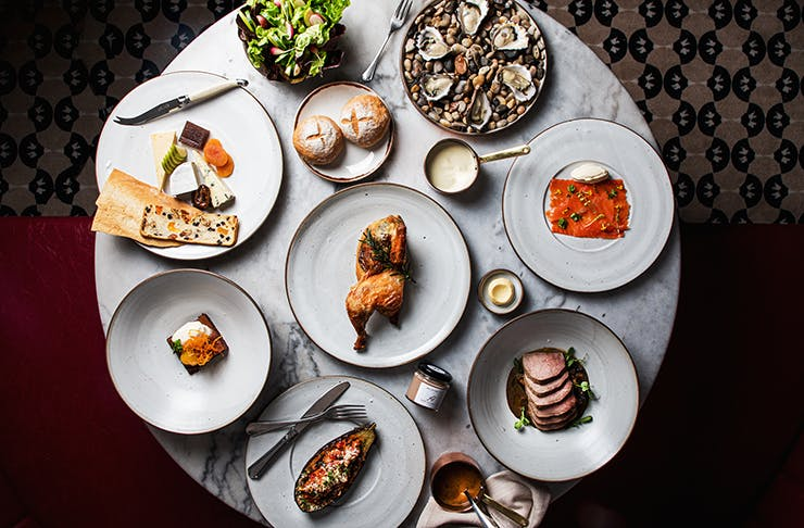 A feast from Hemingway's Wine Room on a round table. A roast chicken studded with truffle sits in the middle as the centrepiece.