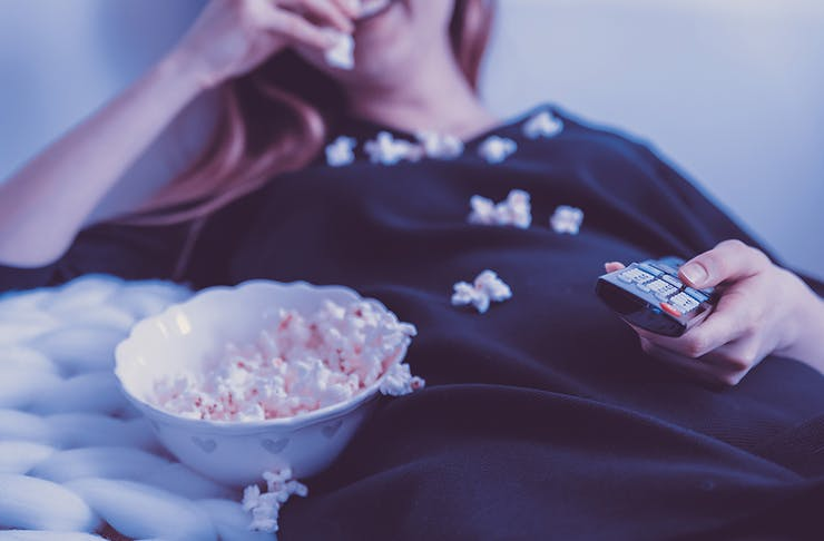 Woman lying on sofa with popcorn