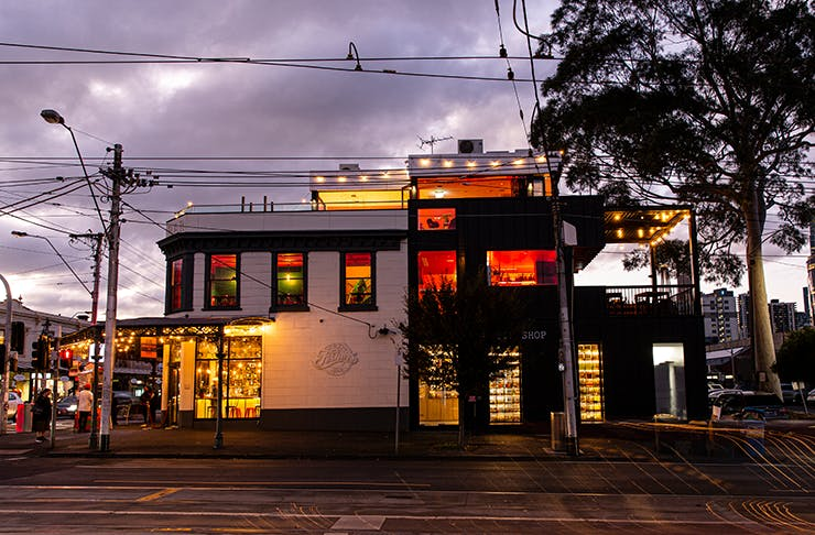 A pub drenched in red lights in the twilight.