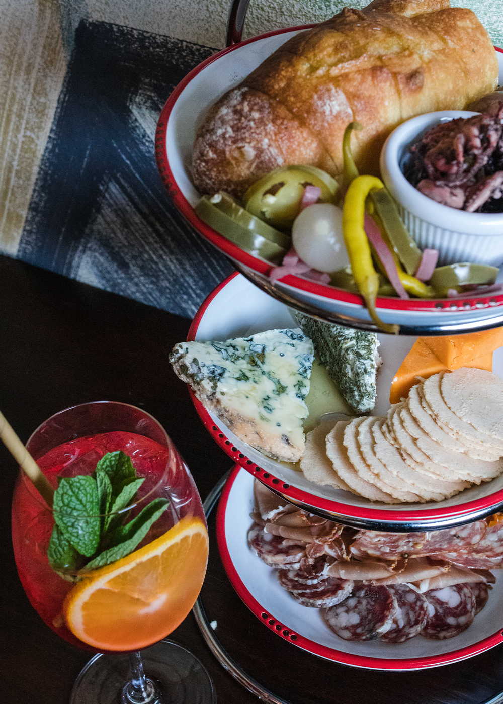 a tower of three plates of cheese and charcuterie