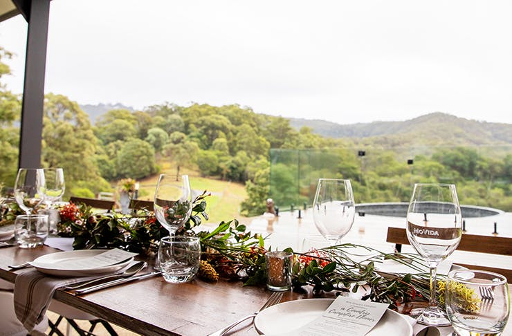 A beautiful long lunch table setting with a picturesque hinterland view in the background.