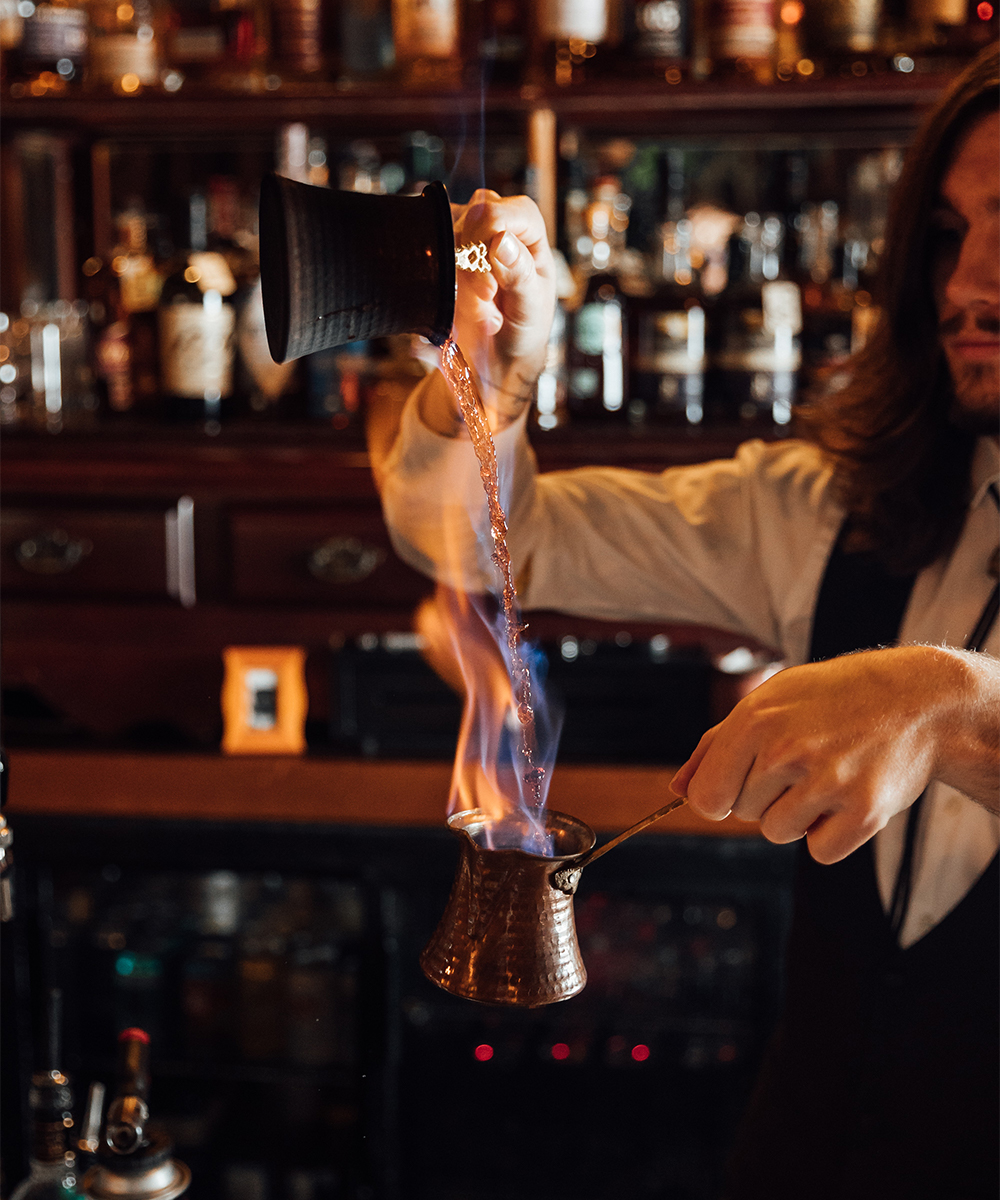 a bartender making a cocktail with fire