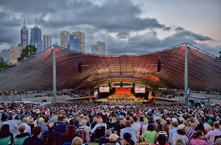 People sitting in front of a massive open-air music stage.