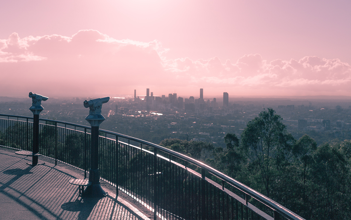 The view from the top of Mt Coot-tha, with Brisbane CBD in the distance and a pink sunset colouring the image