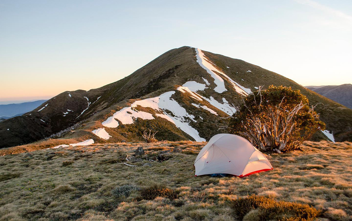 a small tent in front of snow covered hill