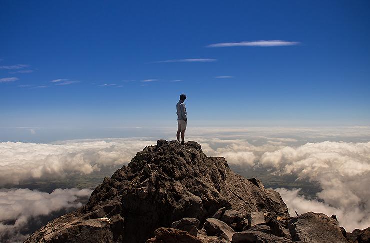 A man stands atop Mount Taranaki looking at nothing but sky.