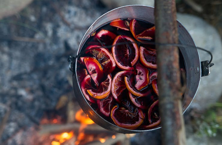 A pot of mulled wine over a campfire.