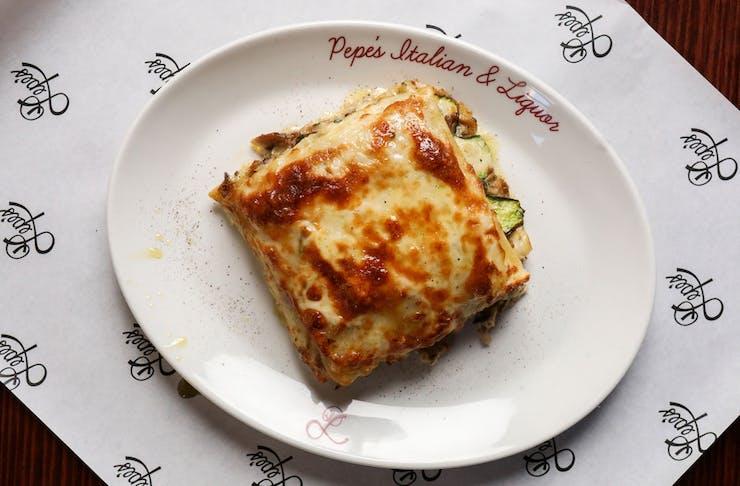 A slice of mushroom lasagne on a plate that says Pepe's Italian & Liquor.