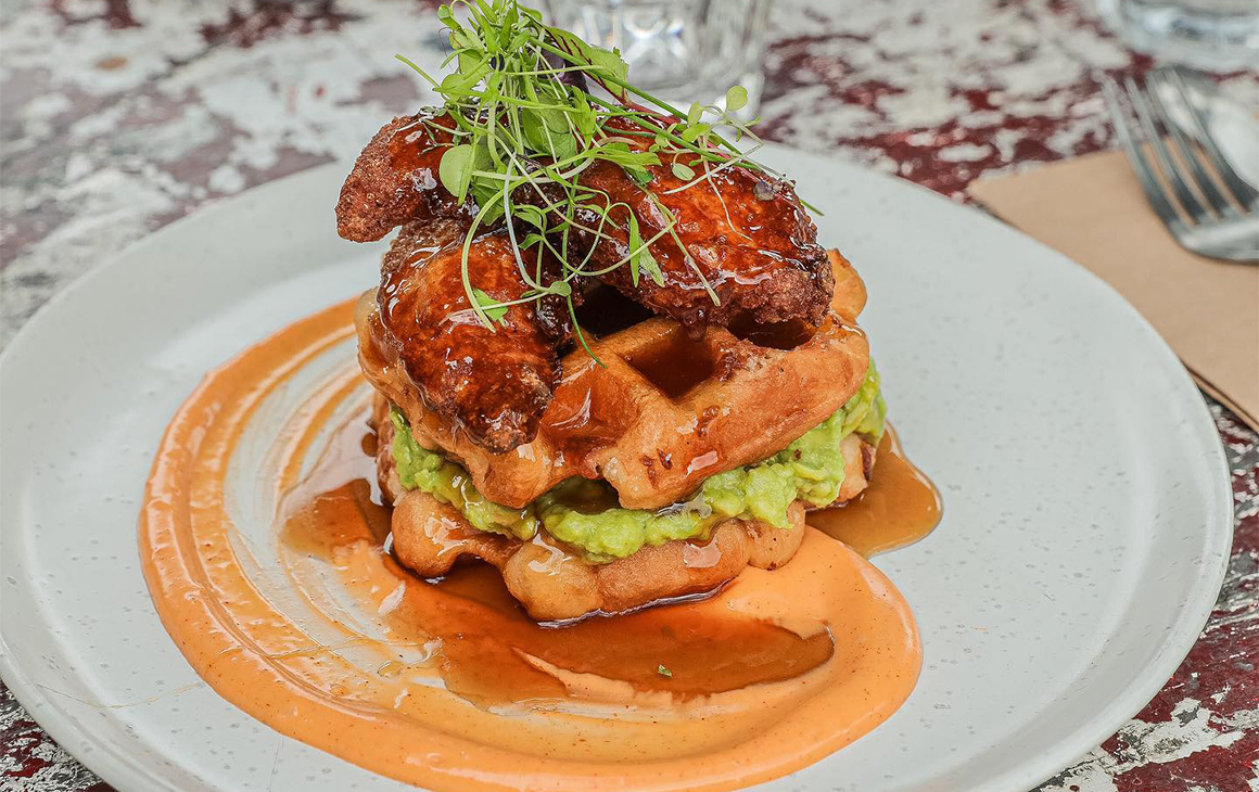 a waffle with avocado and fried chicken