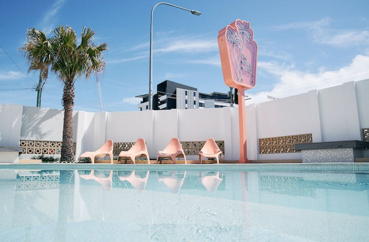 the exterior of a retro motel with kidney shaped pool and a neon pink sign and a palm tree
