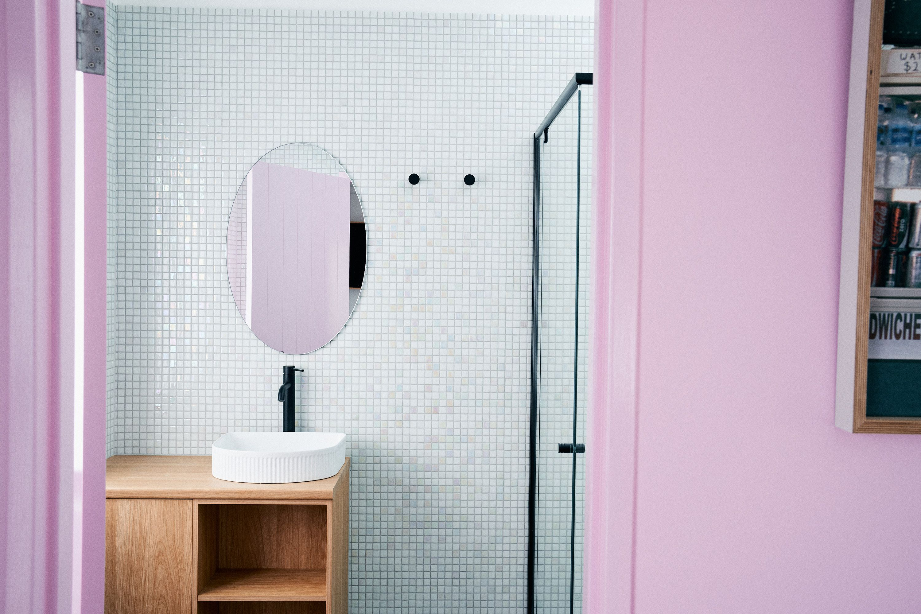 a pink bathroom with white tile and an oval mirror