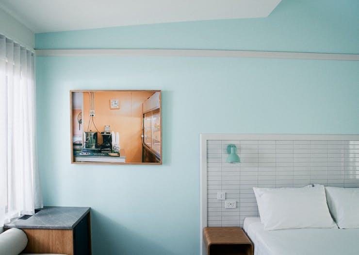 a motel room with a turquoise wall and a retro painting