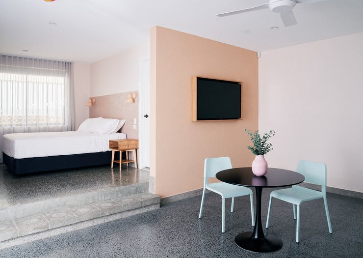a motel room with a small table with turqoise chairs and a salmon pink wall and a tv