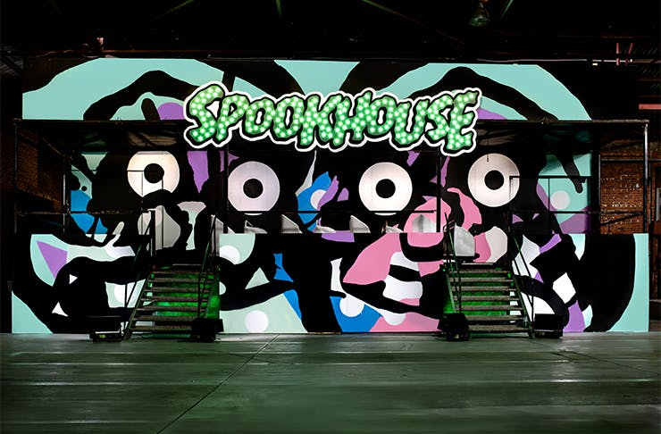a painted neon mural that says SPOOKHOUSE