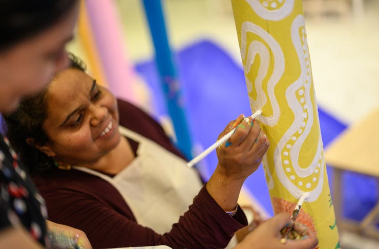 two women painting an Aboriginal totem for NAIDOC week in Perth
