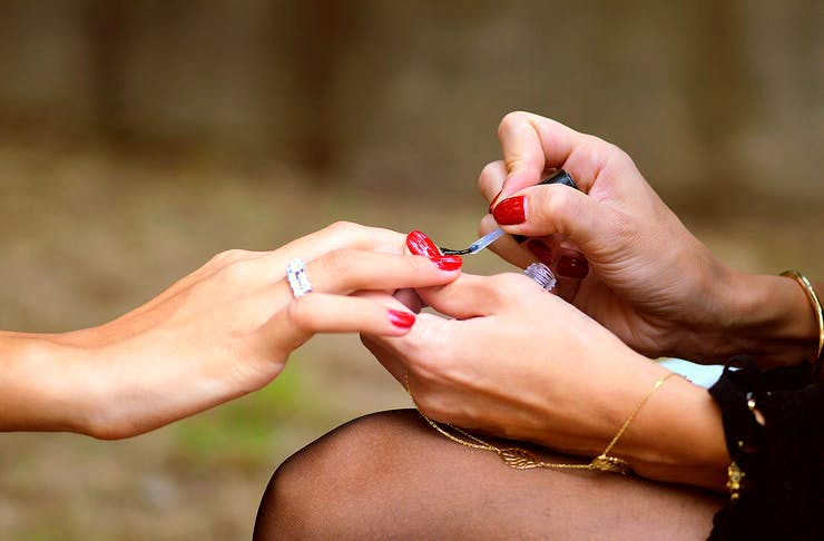 A girl gets her nails done by someone else.