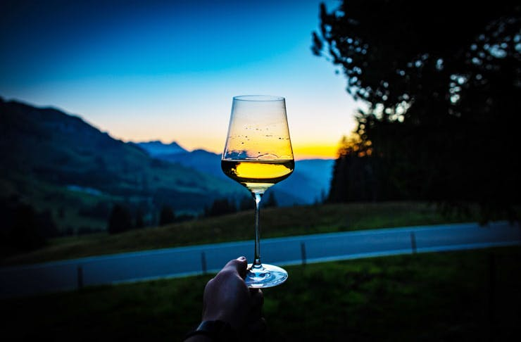 A glass of white wine being held up to the sunset.