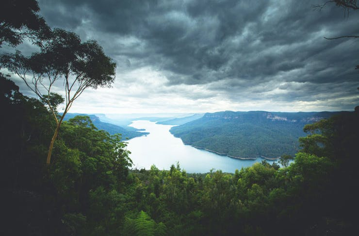 A view of the Blue Mountains National Park, you can see a river in the middle ground and storm clouds forming over head.
