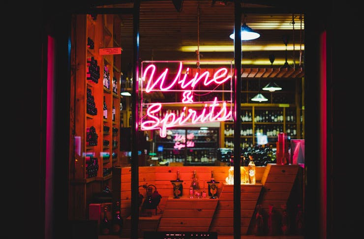 A bottle shop store front at night, with pink neon lettering that reads