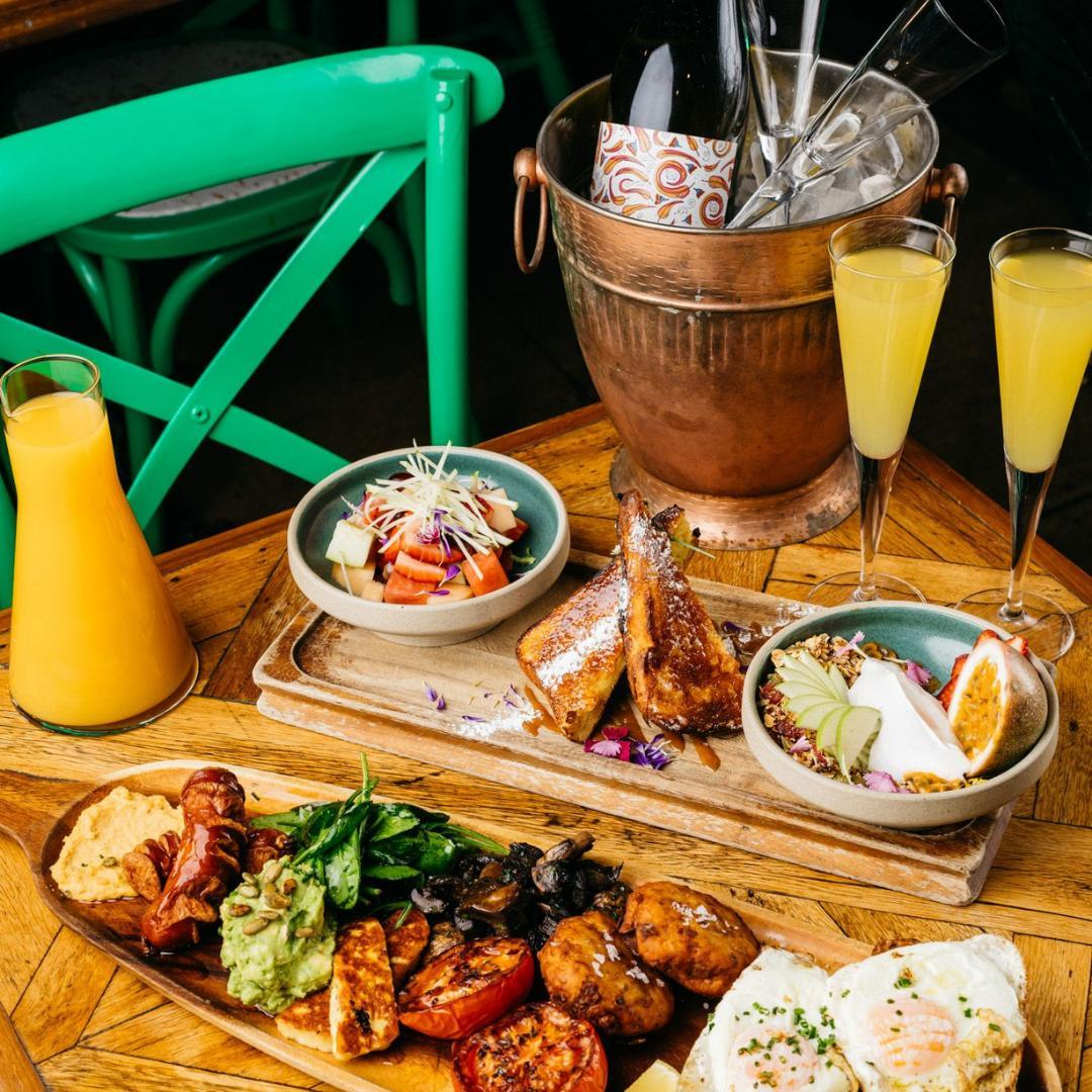 cocktails and breakfast dishes arrayed on a table