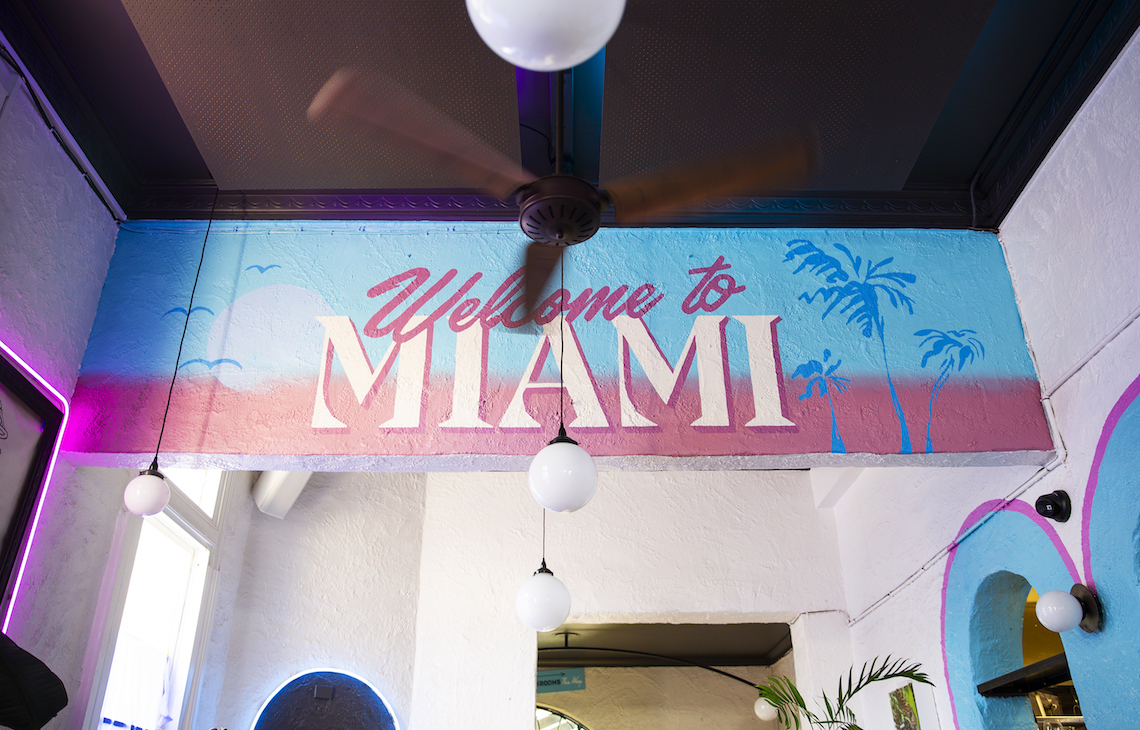 Interior of Neon Palms with Welcome To Miami sign