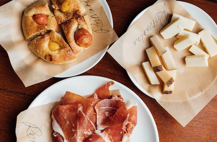plates of cheese, focaccia and prosciutto