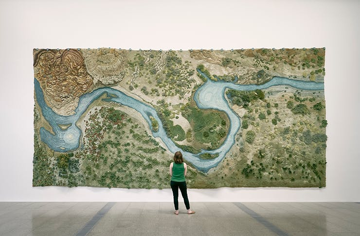 A woman looking at a large painting.
