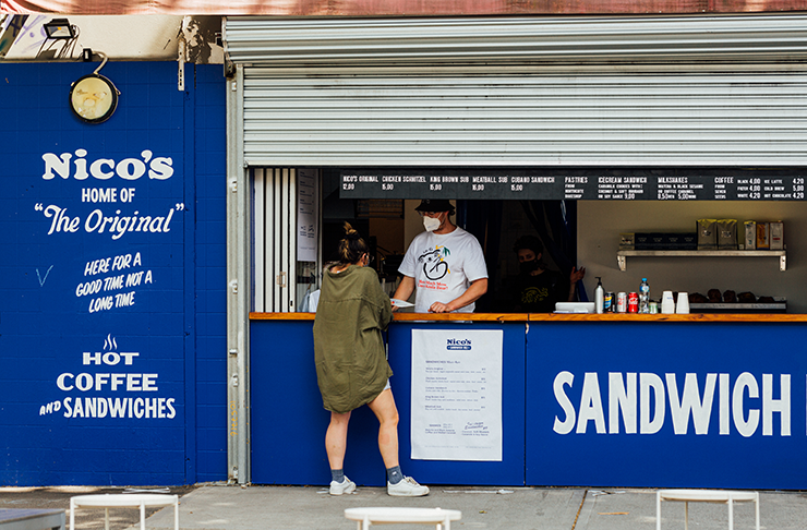 A sandwich store behind a roller door, painted royal blue.