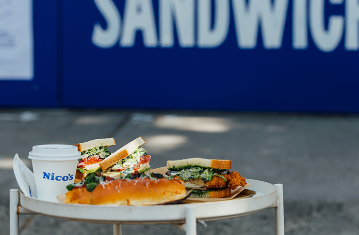 Three sandwiches on a stool in front of a blue wall.
