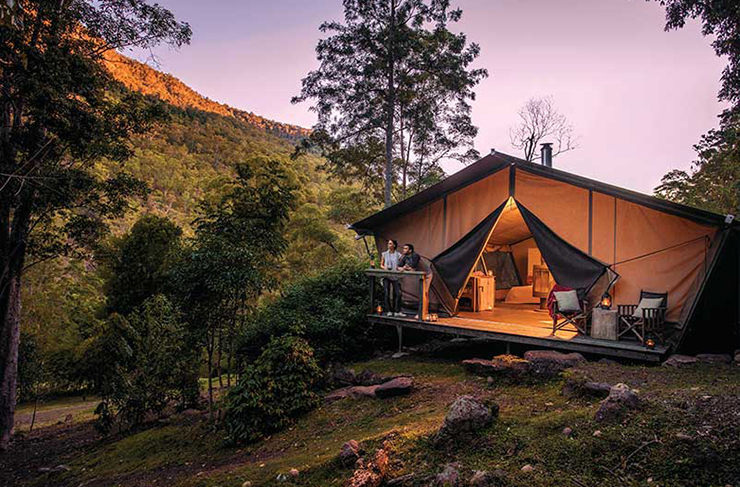 a luxe glamping tent outdoors at sunset