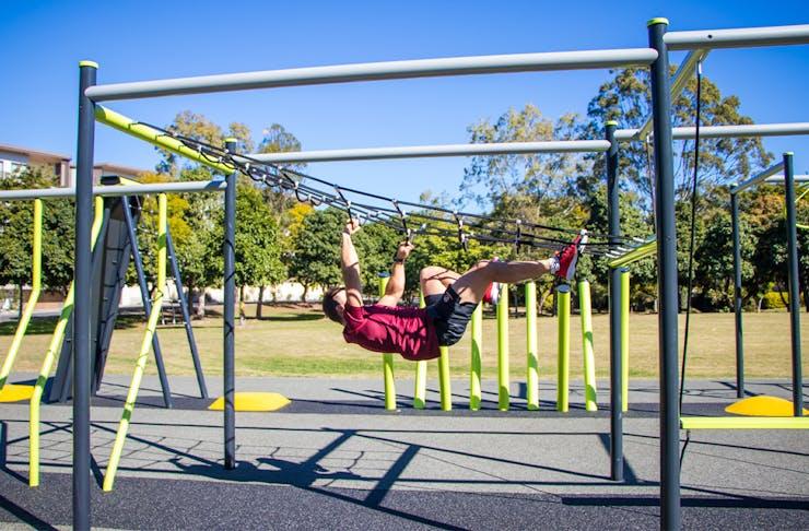 a man climbing a across a rope ladder upside down