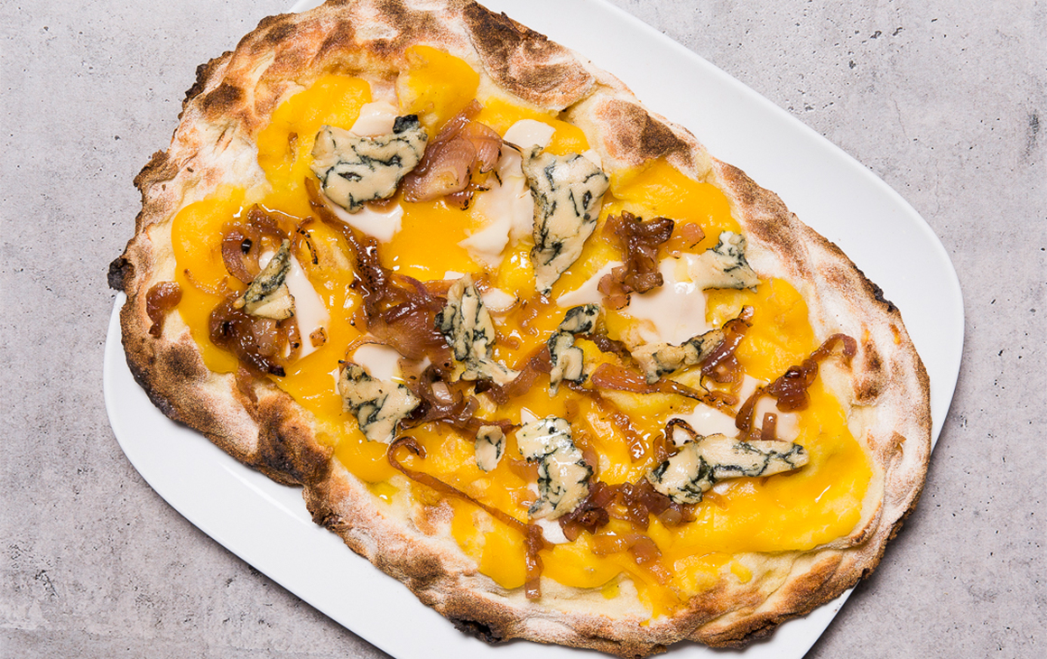 Pizza topped with blue cheese and pumpkin sauce