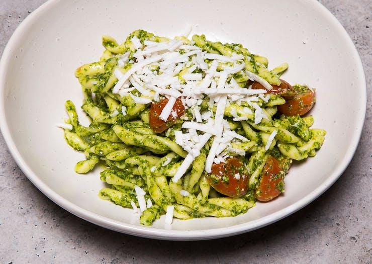 bowl of pesto pasta sprinkled with vegan cheese